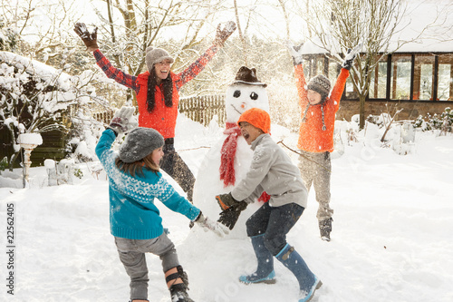 Mother And Children Building Snowman In Garden - 22562405