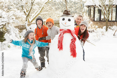 Family Building Snowman In Garden - 22562406