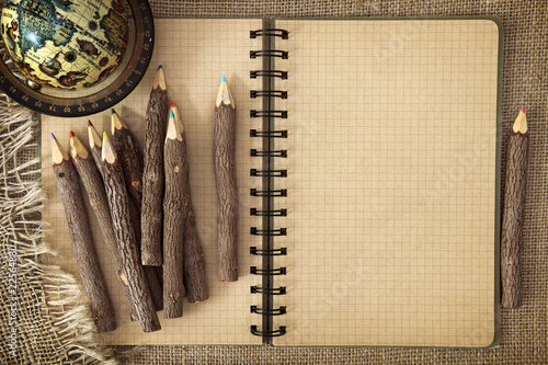 Open exercise book with pencils on brown background