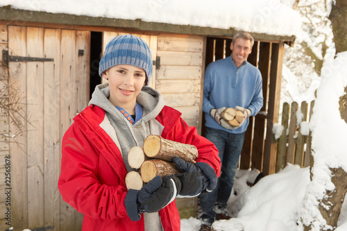Young Couple Collecting Logs From Wooden Store In Snow