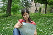 adventure girl with a map of the city lies on the grass