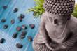 Buddha mit Bambus, Massage Steinen und Schale mit Blüten - 22584225