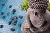 Fototapety Buddha mit Bambus, Massage Steinen und Schale mit Blüten