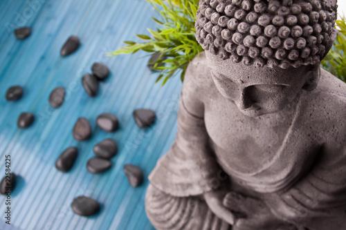 Buddha mit Bambus, Massage Steinen und Schale mit Blüten