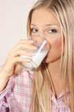 Woman in pajama in bed with glass of milk poster