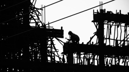 Construction site and workers silhouette