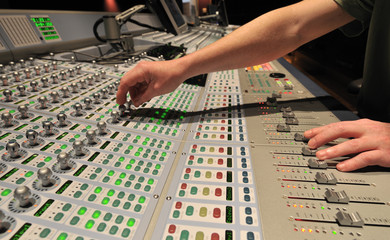 Audio engineer operating mixing console