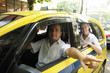 taxi driver showing passenger a landmark