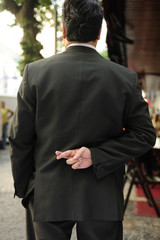 liar: businessman with fingers crossed behind his back