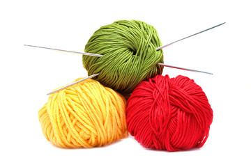 Three balls of wool with knitting needles isolated on white back