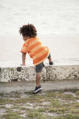 Young child climbing on a ledge