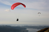 Two paragliders flying over Norwegian coastal landscape