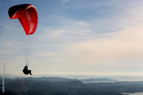 Paraglider flying over Norwegian coastal landscape