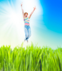 cheerful woman jumping at the green field