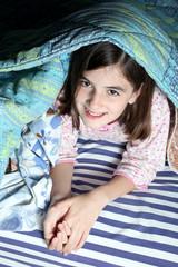 bambina sorridente sotto le coperte