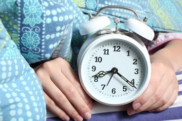 mani mostrano sveglia sul letto