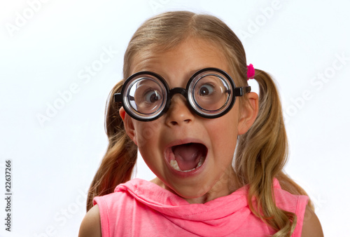 Little girl wearing big round glasses makes a silly expression