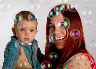 Mother and her baby son enjoy looking at bubbles