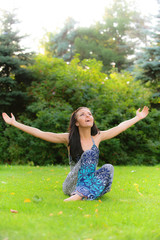 Girl sits on lawn and lifts upwards hands