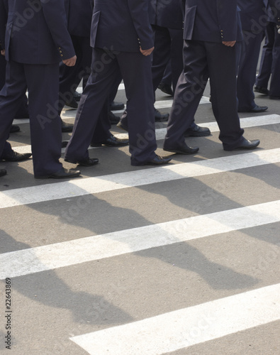 Marched soldiers at a pedestrian crossing of urban street