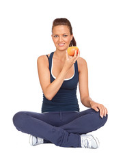 Gymnastics girl with an apple sitting with cross-legs