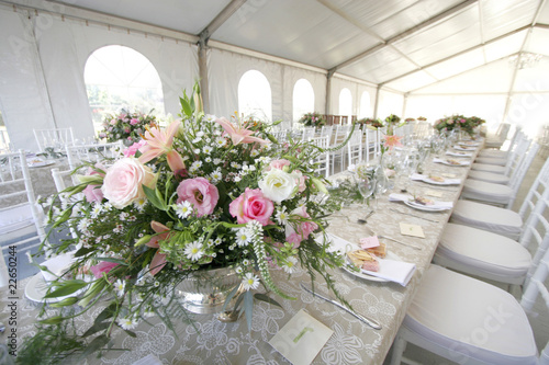 A table setup for a wedding reception in a big tent - 22650244