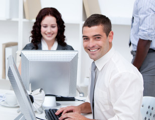 Smiling young business people working at computers