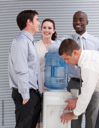 Smiling multi-ethnic business people interacting at a watercoole
