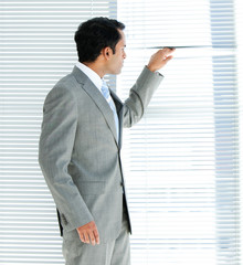 Confident businessman looking through a window