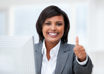 Happy businesswoman with a thumb up working at a computer