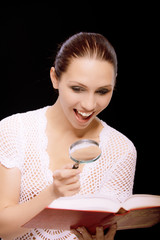 Enthusiastic young woman reads book through magnifier