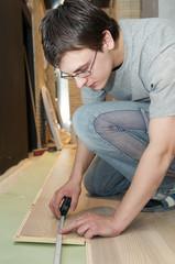 worker measuring at flooring works