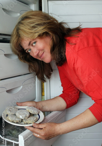 A woman gets out of the refrigerator frozen meatballs