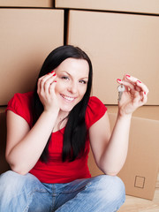 woman sitting with cartons and holding keys to flat