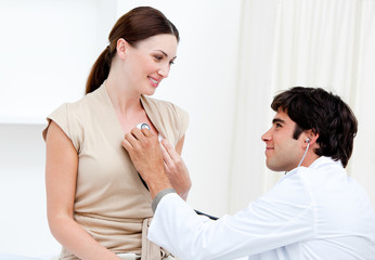 Male doctor examining  a smiling female patient with his stetho