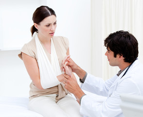 Young male doctor examining the female patient by taking her arm
