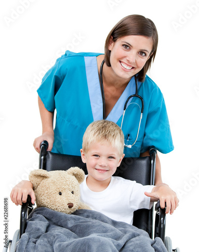 Nice female doctor carrying adorable little boy in the wheelchai