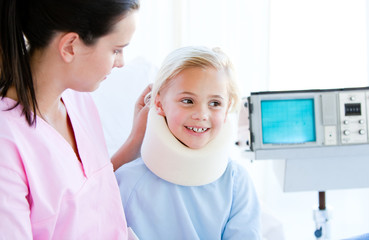 Adorable little girl with a neck brace sitting with her nurse