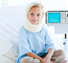 Little girl with a neck brace sitting on a hospital bed