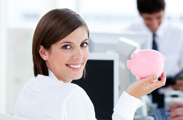 Happy businesswoman holding a piggybank
