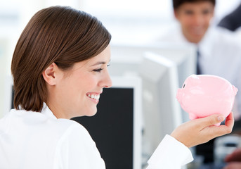 Smiling businesswoman holding a piggybank