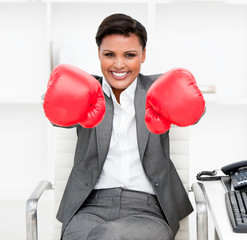 Attractive businesswoman wearing boxing gloves sitting at her de