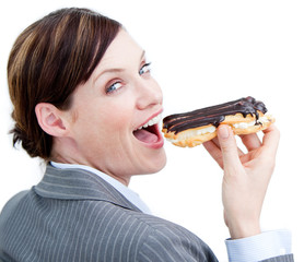 Glowing businesswoman eating a chocolate eclair