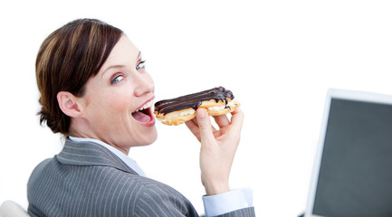 Delighted businesswoman eating a chocolate eclair