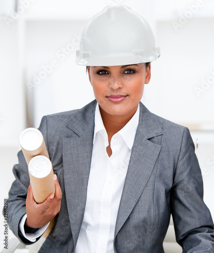 Confident female architect holding blueprints