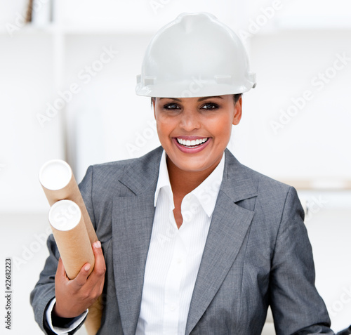 Positive female architect holding blueprints