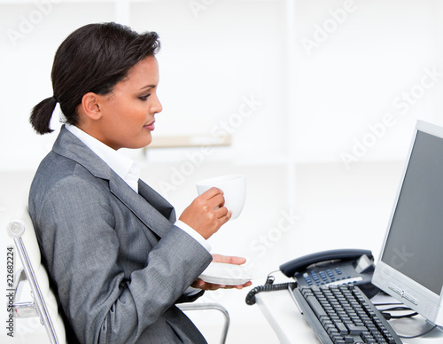 Attractive businesswoman drinking a coffe while working at a com