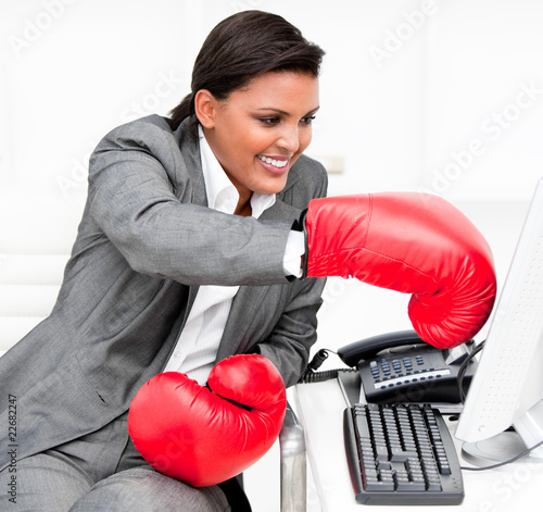 Young businesswoman wearing boxing gloves punching a computer