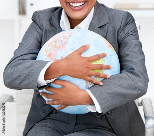 Close-up of a smiling businesswoman holding a terrestrial globe