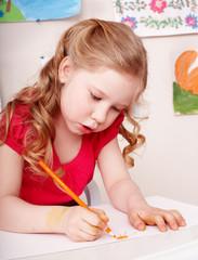 Child with colour pencil draw in preschool.